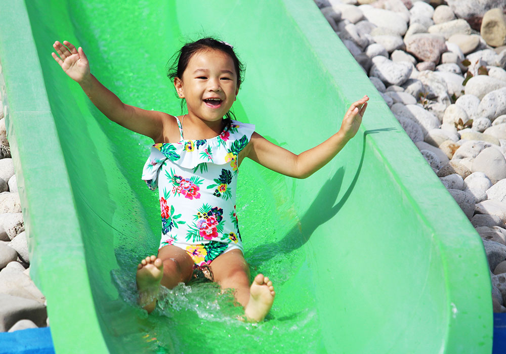 Little girl on green slide at misumu wet play